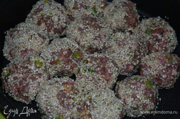 Смоченными в холодной воде руками сформировать из фарша одинаковые колобки-шарики и запанировать их в кунжуте, далее уложить их в форму смазанную маслом, в которой будете запекать блюдо