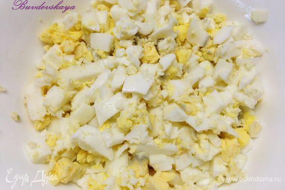 Яица очистить и нарезать мелкими кубиками и переложить в салатник.