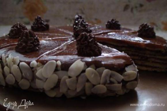 Для приготовления глазури растопить в маленькой кастрюле сахар со сливочным маслом и распределить на торте. Разровнять глазурь ножом, смазанным растительным маслом, и разделить карамельную поверхность на сегменты. Дать карамели застыть. Из кондитерского мешочка выдавить розочки по краю торта.