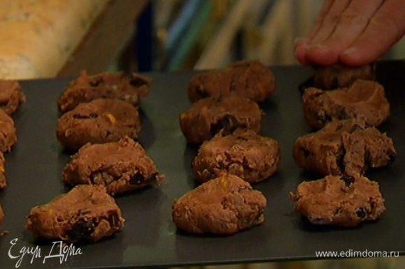 Охлажденное печенье вынуть из холодильника, слегка прижать шарики руками, чтобы получились лепешки, и выпекать в разогретой духовке 15–17 минут.