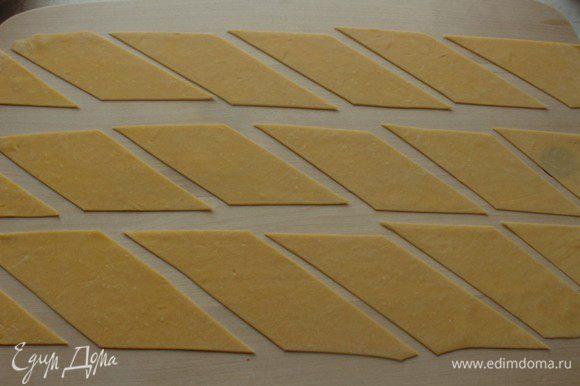 Нарезать тесто на полоски, а затем на ромбы.