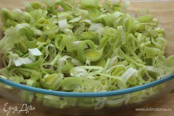 Порей (белую часть) нарезать тонкими кольцами и выложить в смазанную оливковым маслом форму для запекания.