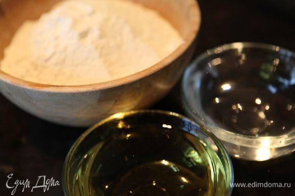 В миску влить стакан горячей воды, добавить соль, сахар, масло растительное. Все перемешать и постепенно всыпать муку.