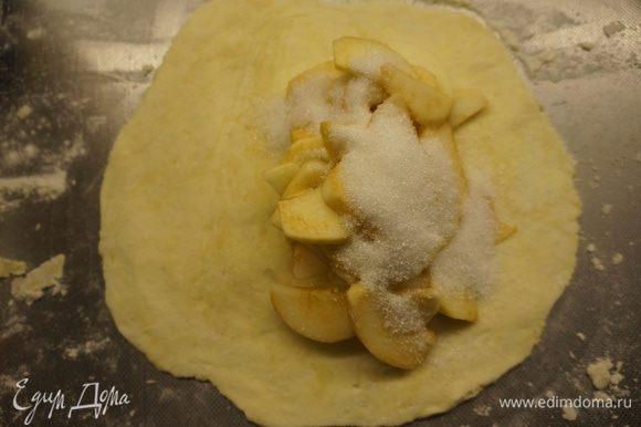 Достать тесто из холодильника, разделить на 5 - 6 частей. Каждую часть раскатать в блинчик, не очень тонко. А затем по принципу лепки вареников, на одну половину блина положить начинку из яблок и посыпать сахарным песком - 1-2 десертных ложки в каждый пирог.