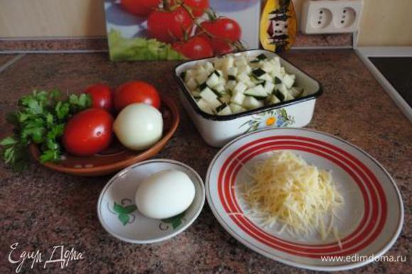 Яйцо залить холодной водой и поставить варить на 10 минут. Духовку включить для разогрева до 220-250 градусов. Кабачки очистить (если кабачки молодые с нежной кожицей, то чистить не надо), нарезать на кубики. Лук мелко порубить. Помидоры нарезать кубиками.