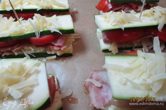 Сверху на каждый кусочек кабачка положить грудинку и помидоры. Накрыть оставшимися кусочками кабачка. Скрепить зубочисткой. Посолить, поперчить. Посыпать оставшимся сыром. Поставить в духовку на 10 мин.