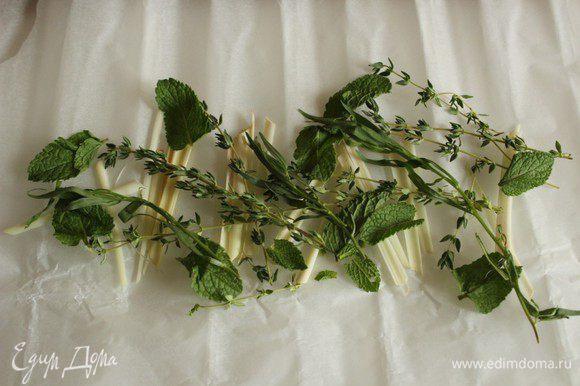 На лист пергамента выложить половину веточек трав и порезанный стебель лимонного сорго.