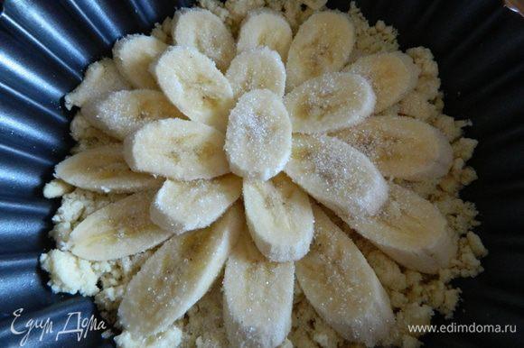 Достаем тесто из холодильника, высыпаем его в форму для выпечки, разравниваем, сверху выкладываем бананы и посыпаем их 1 столовой ложкой сахара, все отправляем в разогретую духовку на 15-20 минут.