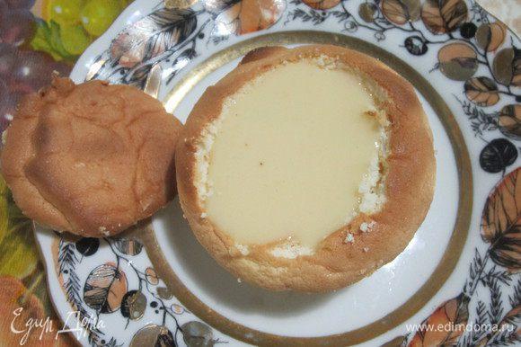 Со стороны плоской поверхности вырезать аккуратно «шапочку» (сохранить её). Наполнить заварным кремом и закрыть шапочкой. Сделать пропитку. Смешать свежевыжатый апельсиновый сок с сахаром. Вскипятить и остудить. Очень быстро опустить пирожные выпуклой стороной в сироп и перевернуть донышком вниз. Поставить в холодильник на 1-2 часа.