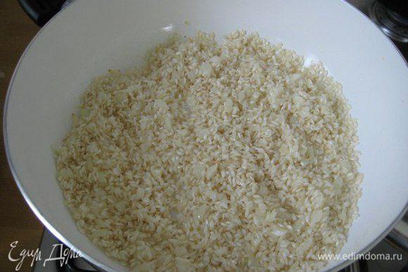В отдельную сковородку положить масло сливочное, добавить мелко порезанный лук, обжарить лук до прозрачности, добавить рис, перемешать и добавить белое вино.