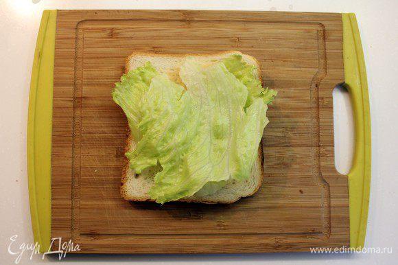На подсушенный хлеб положить листик салата.