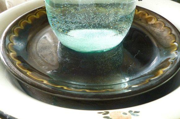 Достать баклажаны из кастрюли, сложить в миску, сверху накрыть крышкой или тарелкой, поставить небольшой груз, оставить на 1 час, чтобы ушла горечь.