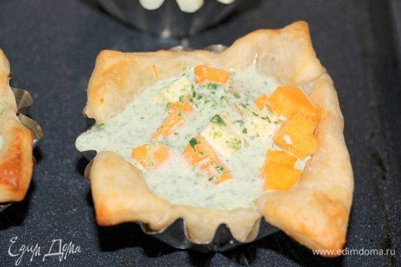 В подготовленные тарталетки выложить кубики тыквы и феты, залить шпинатно-сливочной смесью.