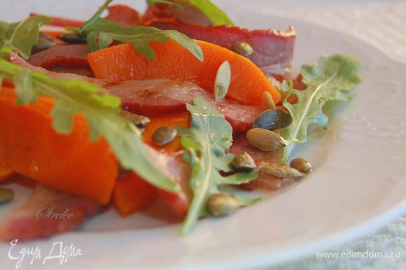 В тарелку выложить ломтики тыквы, бекон и семечки. Слегка перемешать. Украсить рукколой. Сбрызнуть оливковым маслом. Приятного аппетита!