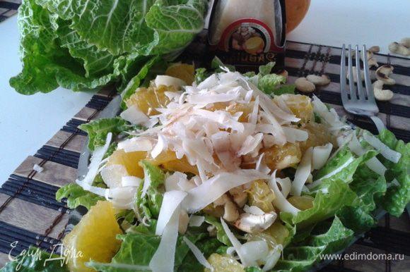 Выложить на тарелку листья капусты и апельсин, полить заправкой. Затем посыпать орешками, и хлопьями потереть сыр Джюгас 12 месяцев выдержки.