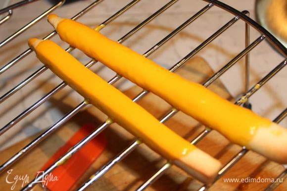 Каждую заготовку для карандашей обмазать глазурью (держать за кончик и с помощью ложки наливать на карандаш глазурь). Лучше разместить их на решетку, чтобы лишняя глазурь могла свободно стекать.