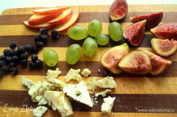 Инжир разрезать на 4 части, яблоко порезать тонкими дольками. Виноград оборвать с веточки и помыть. Чернику помыть и просушить на бумажной салфетке. Сыр порезать небольшими кусочками, орехи очистить от скорлупы и порезать крупными кусочками.