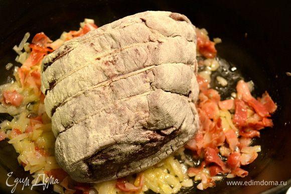 Мясо достать из маринада, обсушить бумажным полотенцем, обвалять в муке и положить обжариваться в кастрюлю с луком и беконом.