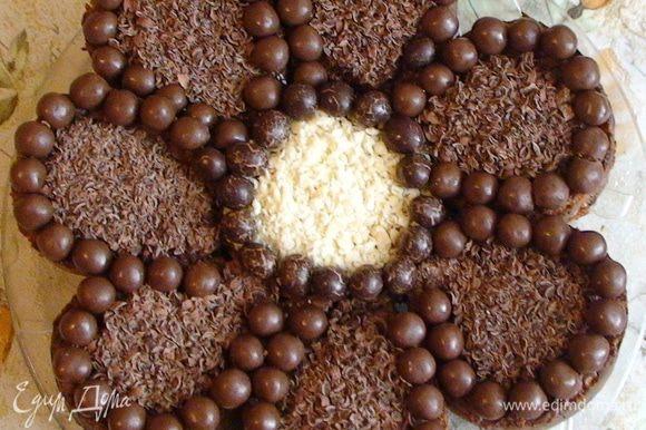 Выложить каждый лепесток и серединку торта маленькими круглыми конфетками (у меня рисовые шарики в шоколаде). Присыпать серединку тертым белым, а все лепестки тертым черным шоколадом. Если есть разноцветная кокосовая стружка – можно вместо шоколада каждый лепесток оформить разным цветом – получится «цветик-семицветик». Или украсить любым другим способом – по вашему вкусу и фантазии.