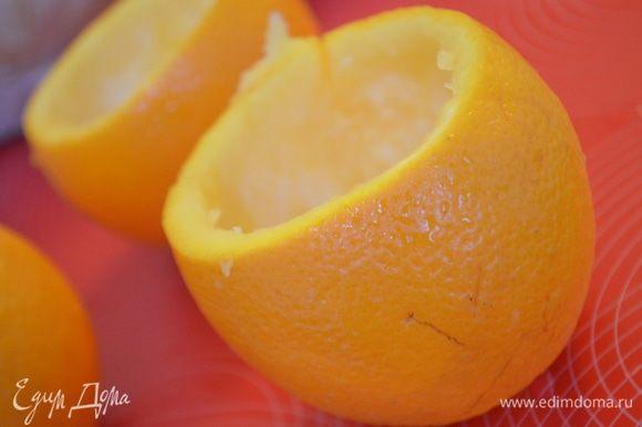У апельсинов срезать верхушки. Мякоть убрать большой ложкой так, чтобы не повредить кожуру.