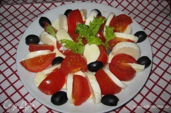 Выложите сыр вперемешку с помидорами на 4 индивидуальные тарелки. Посолите и поперчите по вкусу. Смешайте оливковое масло с соусом песто и полейте этой смесью сверху каждой тарелки. Украсьте маслинами, базиликом (у меня листья салата) и подавайте на стол.