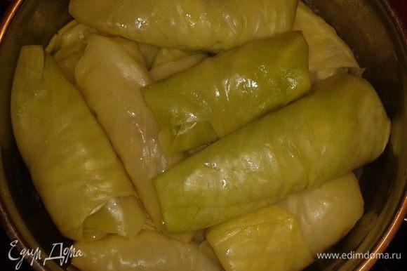 В капустный лист положить начинку из фарша и риса, завернуть в трубочку и выложить в кастрюлю, где 1 слой - лук и морковь.