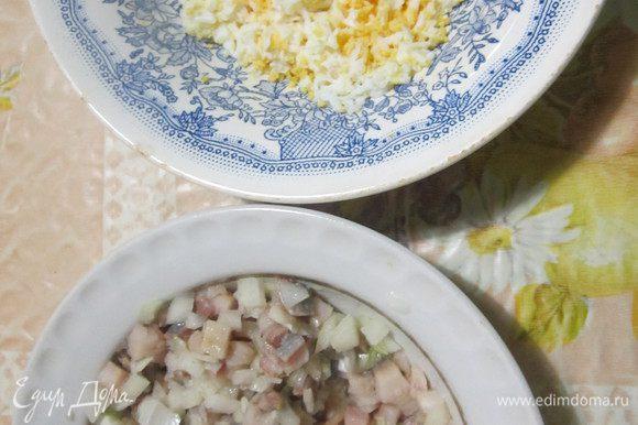 Лук мелко нарезать. Филе сельди нарезать маленьким кубиком, добавить лук и перемешать. Яйца сварить, очистить и натереть на мелкой терке.