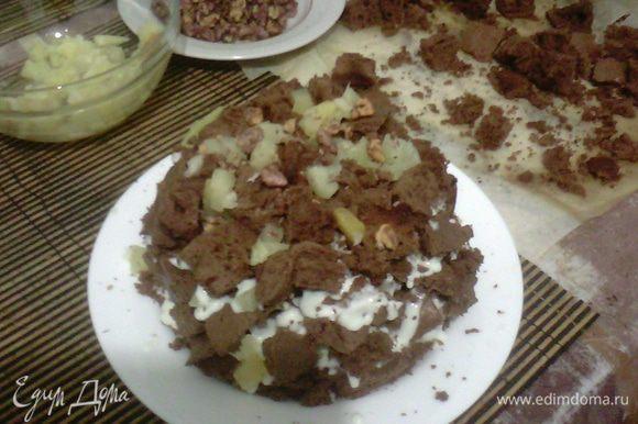 Выкладываем торт горкой, сверху смазываю кремом и украшаю орехами и ананасом.