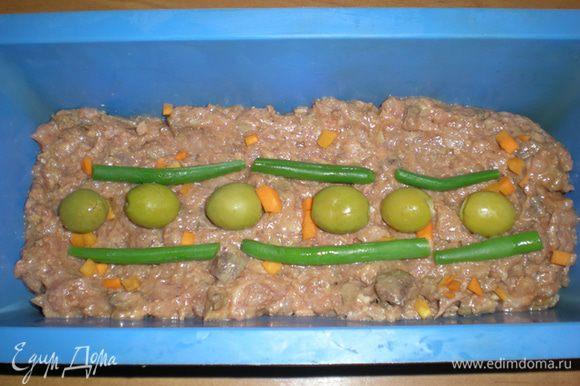 Морковь нарежьте маленькими кусочками. Я клала ее в фарш сырую. Стручковую фасоль отварите минуты три. Выложите в силиконовую форму треть фарша, разложите морковку, фасоль и оливки.