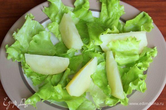 Промытые и обсушенные листья салата порвите уложите на дно блюда (или порционных тарелок). В один слой на небольшом расстоянии друг от друга разместите кусочки картофеля.