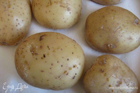 Положить на противень на толстый слой соли. Наколоть вилкой, чтобы кожура не потрескалась. Поставить противень в разогретую до 200 градусов духовку на 1 ч. Может понадобиться чуть больше времени, необходимо проверить картошку, проколов вилкой.