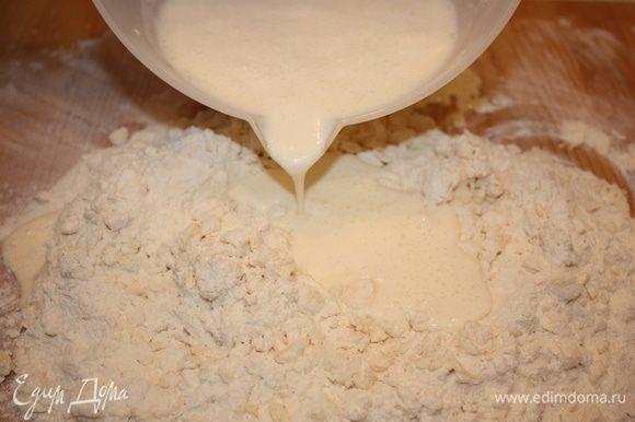 Выливаем подготовленную смесь в муку с маргарином и быстро замешиваем мягкое тесто.