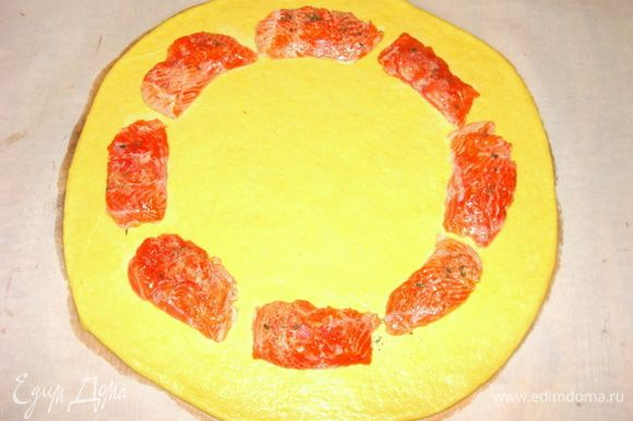 Раскатать ровный круг, толщиной 7-8 мм. Выложить рыбу по кругу, отступая примерно 4 см.