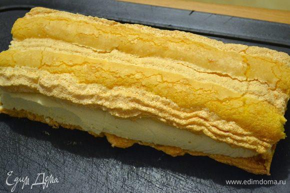 Положить первый бисквит на разделочную доску, рельефной стороной вниз. Крем, если делали в квадратной форме, разрежьте напополам или под размеры ваших полосок. Положите на одну полоску бисквита и накройте второй.