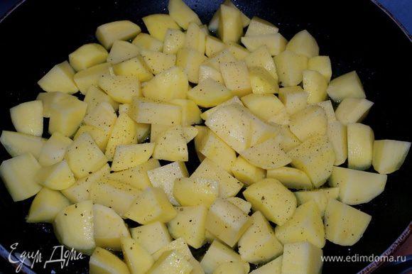 В большую сковороду налить оливковое масло и положить обжариваться картофель. Посолить и поперчить по вкусу. Обжаривать 5 минут на сильном огне. Затем накрыть крышкой, уменьшить огонь и продолжать готовить еще 20 минут, время от времени осторожно перемешивая (или встряхивая) картофель.