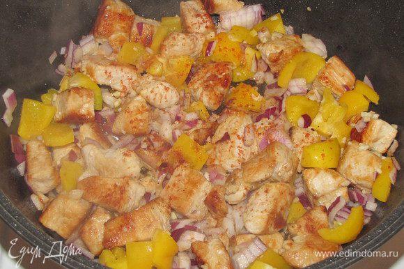 Затем вернуть все мясо в кастрюлю, добавить лук, чеснок и сладкий перец, а так же немного острого красного перца. Перемешать, закрыть крышкой и готовить на среднем огне 15 минут, время от времени помешивая.
