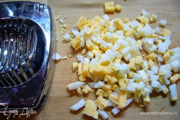 Кальмары почистить, опустить в соленую кипящую воду (соль – из расчета 1 ст. л. на 1 литр воды), варить 3 мин. Остудить. Порезать. Яйца отварить 7 мин., остудить. Очистить от скорлупы. Нарезать кубиками.