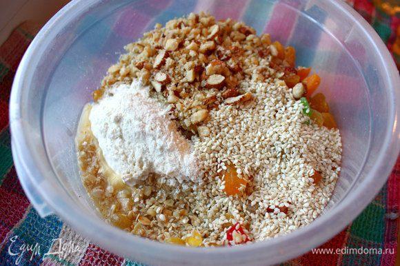Затем в миску с овсянкой добавить орехи, кунжутные семечки, цукаты, курагу (заранее нарезанную полосками), изум, масло, муку пшеничную и овсяную. Все тщательно перемешать.