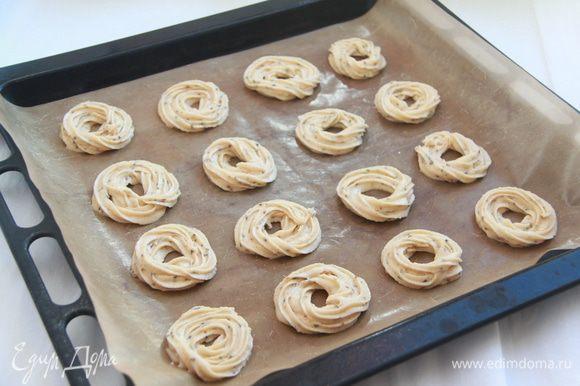 Тесто поместить в кулинарный рукав и выдавить с его помощью колечки на антипригарный лист или пекарскую бумагу.