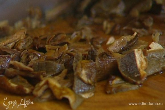 Сухие грибы залить горячей водой и дать постоять, чтобы они стали мягкими, затем воду слить и сохранить, а грибы мелко порезать.