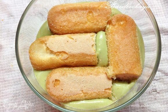 Печенье Савоярди по одному обмакните в сироп (по необходимости разрежьте на кусочки) и выложите на слой крема.