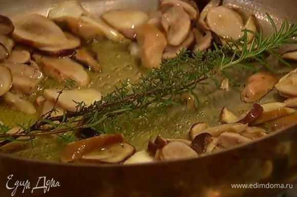 Сковороду, где жарились крутоны, протереть бумажным полотенцем, разогреть в ней 2 ст. ложки оливкового и 1 ч. ложку сливочного масла, выложить грибы, веточки тимьяна и розмарина, половинку луковицы и чеснок, посолить, поперчить, перемешать и, не накрывая крышкой, жарить на медленном огне до готовности грибов.