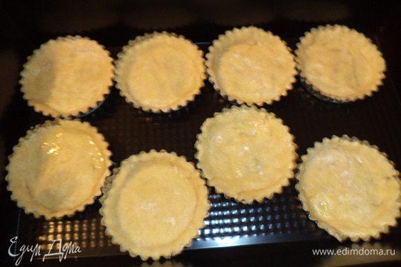 Раскатать тесто в тонкий пласт, вырезать из теста кружочки, и выстелить ими формочки для тарталеток, смазанные маслом. Выпекать 15 минут при температуре 180 градусов.