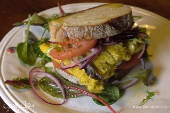 Хлеб сбрызнуть оставшимся маслом Extra Virgin, выложить на оба куска кружки помидора и лук. На один кусок хлеба поместить листья салата, а на другой выложить омлет, затем сложить их вместе.