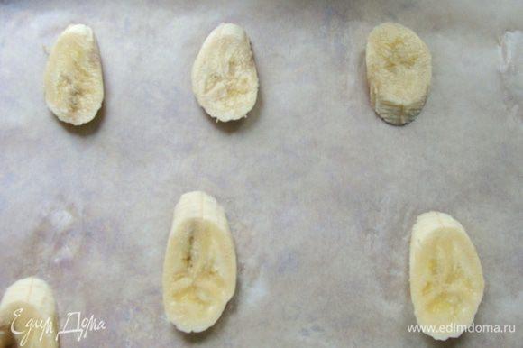 Банан порезать дольками, выложить на противень, застеленный пекарской бумагой, на довольно большом расстоянии друг от друга.