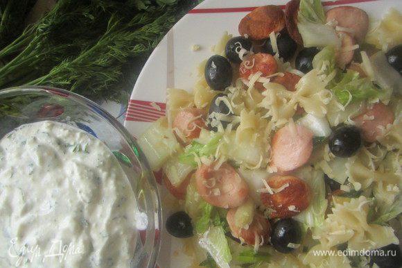Все ингредиенты смешать (сосиски, салат, оливки, пасту), выложить в порционные тарелки, посолить, по желанию посыпать блюдо стружкой сыра. Йогуртовый соус подать к основному блюду в порционных пиалах или в одной большой соуснице.
