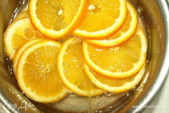 Сахар растворяем в воде, доводим до кипения. Добавляем нарезанные тонкими кружками апельсины и варим 20 минут, пока кожура не станет мягкой.