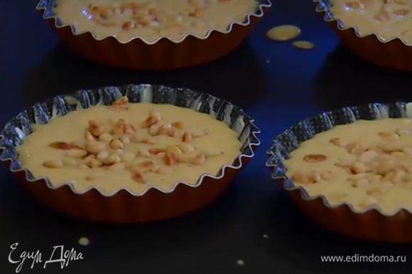 Формочки для тарталеток смазать оставшимся сливочным маслом, разлить в них тесто, посыпать сверху кедровыми орехами и выпекать в разогретой духовке 15–20 минут.