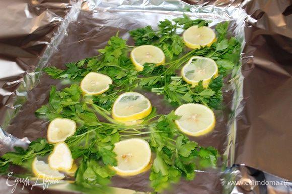 На противень выстелить фольгу в несколько слоев, разложить кружочки лимона и веточки свежей петрушки (по диагонали).