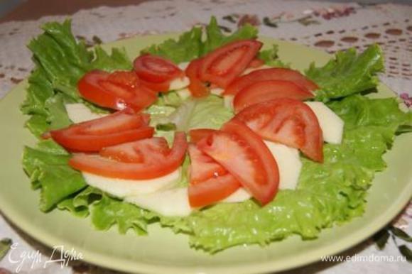 На листья салата выложить яблоки и помидоры.